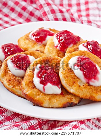 Pancakes of cottage cheese with sour cream and raspberry jam