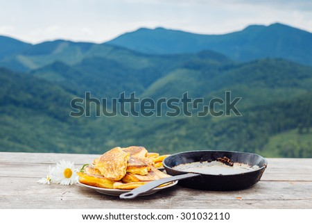 Pancakes on a plate next to the frying pan on a wooden table with mountains on a blurred background - stock photo