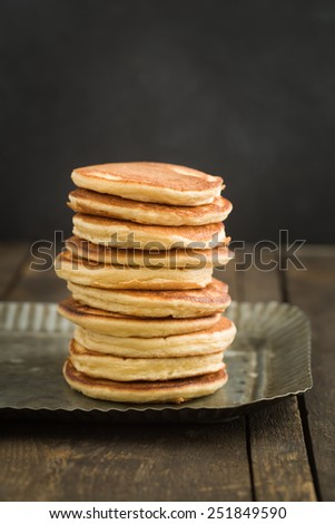 Pancakes piled up on dark wooden background