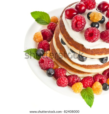 Pancakes stack with fresh forest berries  on white background - stock photo