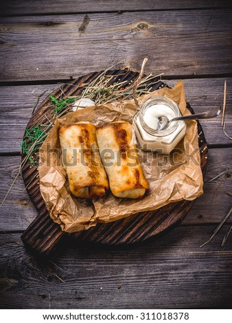 Pancakes with a stuffing and sour cream on a wooden table. Style rustic. Selective focus. - stock photo