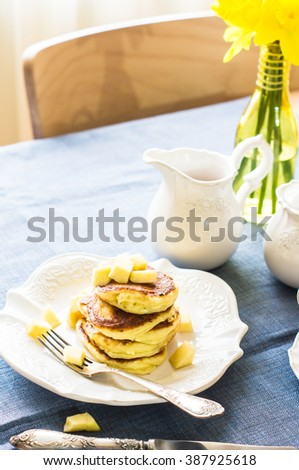 Pancakes with apple and honey with yellow daffodils on the table