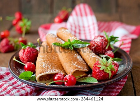 Pancakes with berries and syrup in a rustic style - stock photo