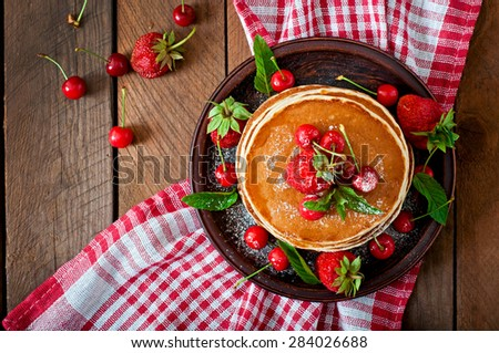 Pancakes with berries and syrup in a rustic style. Top view - stock photo