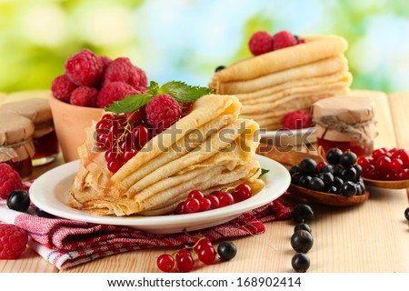 pancakes with berries, jam and honey on wooden table on  green background - stock photo