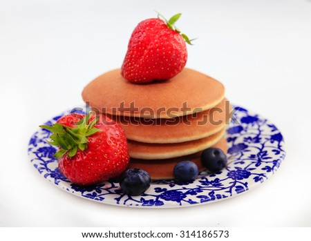 Pancakes with berries on a saucer.