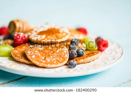 Pancakes with berries on wooden background - stock photo