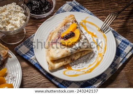 Pancakes with blackberry jam and cheese on a wooden background.