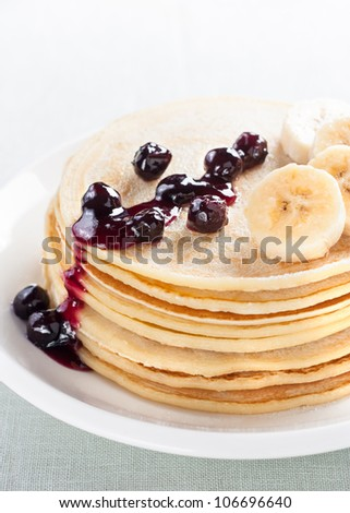 pancakes with blueberries and banana on white plate - stock photo