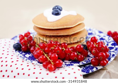 Pancakes with blueberries and currants on a plate.
