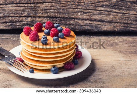 Pancakes with blueberries & raspberry on wood background .