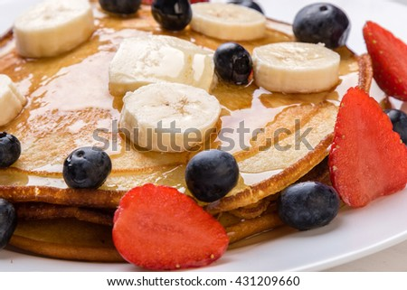 pancakes with blueberry, banana, strawberry and syrup - stock photo