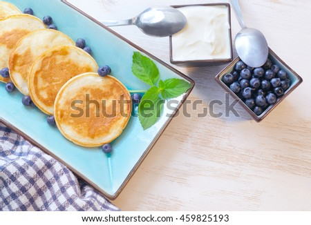 Pancakes with blueberry in rectangular plate and bowls with sour and berries. Overhead view. Tasty pancakes. Photo of  pancakes. Delicious pancakes. Homemade pancakes. Pancakes for breakfast