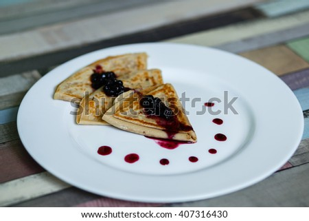 pancakes with blueberry jam on a white plate