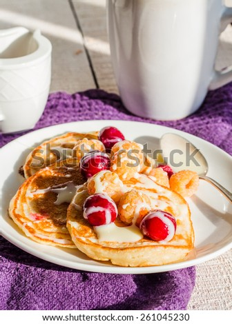 pancakes with cherry, raspberry and vanilla sauce on a white background