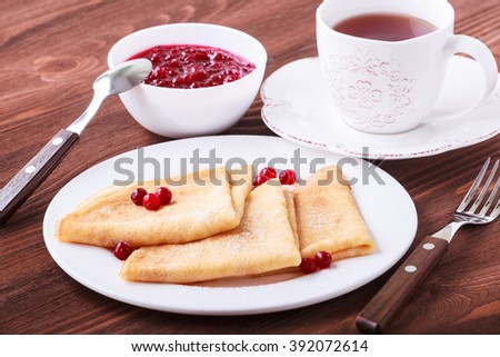 Pancakes with cranberries and tea on a wooden table