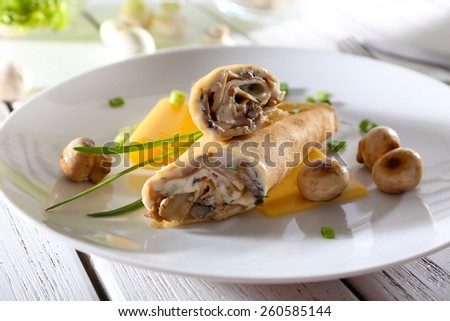 Pancakes with cream and mushrooms on wooden table, closeup - stock photo