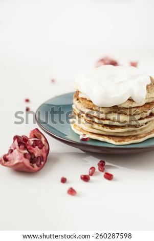 Pancakes with creme yogurt and ripe pomegranate fruit  - stock photo