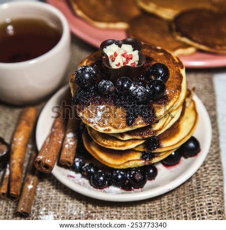 Pancakes with currant jam and a cup of tea - stock photo