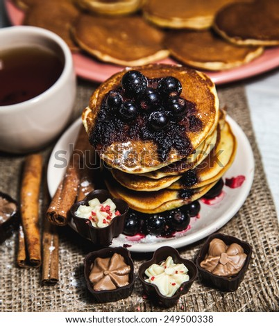 Pancakes with currant jam and a cup of tea. Delicious food. dessert - stock photo