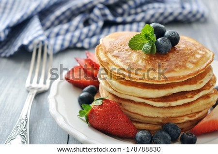 Pancakes with fresh berries, mint and maple syrup on white plate closeup - stock photo