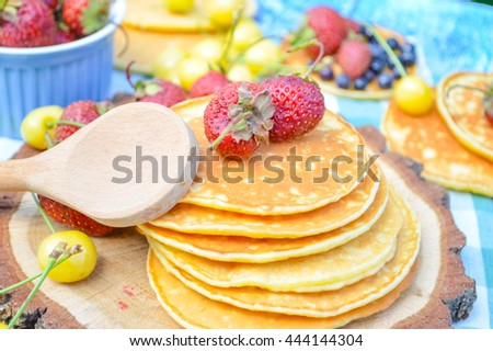 Pancakes with fresh raspberries, strawberries, cherries, blueberries on blue wooden background in garden or on nature . - stock photo