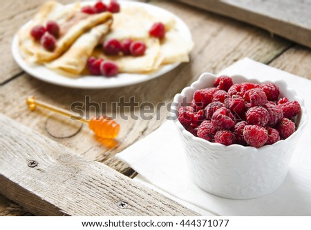 Pancakes with fresh raspberry on the rustic board