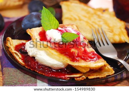 pancakes with homemade plum confiture and whipped cream  - stock photo