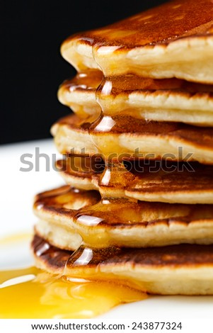 Pancakes with honey and cranberries on a plate. - stock photo