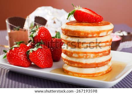 Pancakes with honey and strawberries and candies on background - stock photo