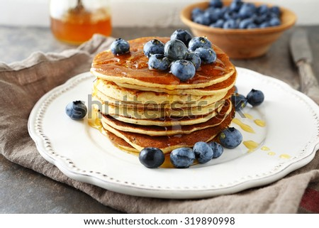 pancakes with honey on plate - stock photo