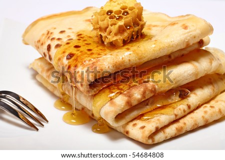 Pancakes with honey on white background