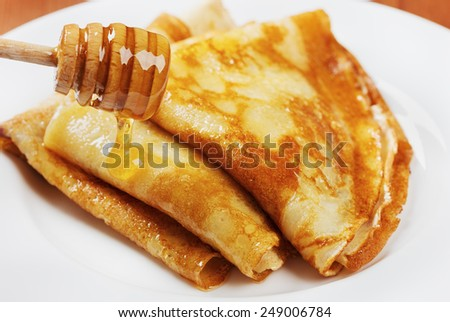 pancakes with honey syrup on a white plate. traditional crepe for pancake week or Shrovetide. shallow DOF. - stock photo