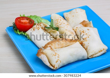 Pancakes with meat served salad leaves and tomato - stock photo