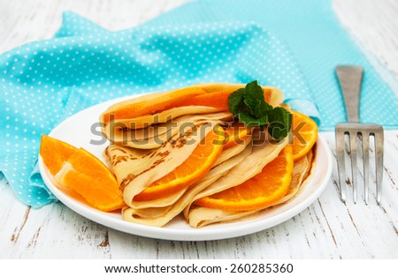 pancakes with orange  on a wooden table