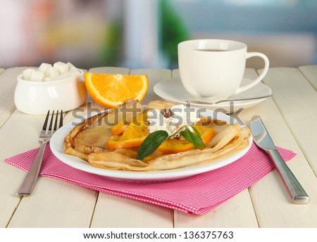 Pancakes with orange on bright background