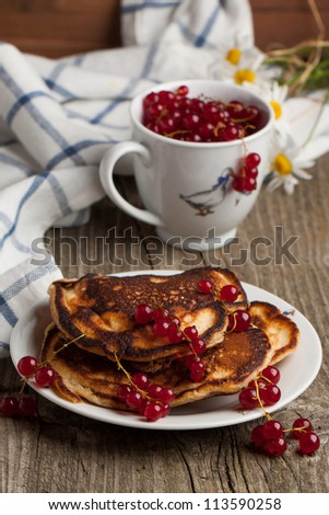 Pancakes with red currant served on old wooden table - stock photo