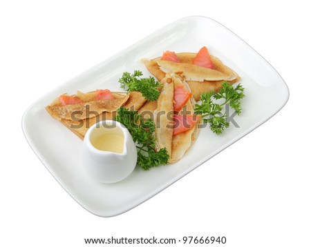 pancakes with salmon and cheese sauce on rectangular white dish isolated on white background. Side view. - stock photo