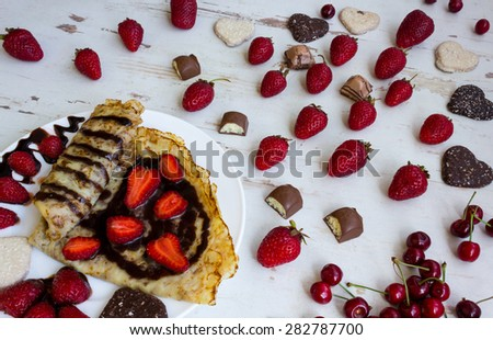 Pancakes with strawberries and chocolate on a white plate on the table. Strawberry, cherry, chocolate, candy and cookies on the table. - stock photo
