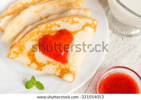 Pancakes with strawberry jam heart shape for traditional romantic breakfast, valentine day concept