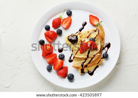 pancakes with summer berries on plate, top view