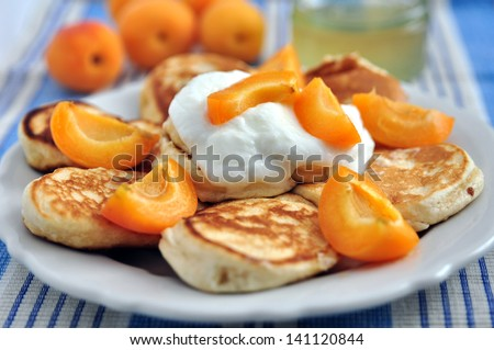 Pancakes with yoghurt and apricots for breakfast - stock photo