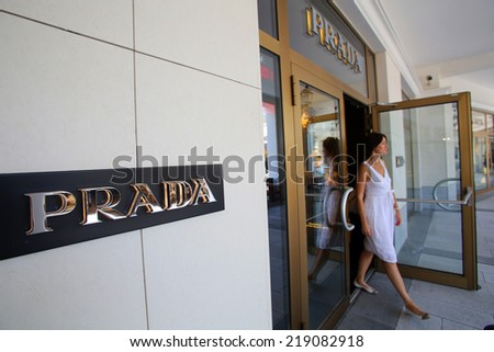 PANDORF, AUSTRIA - AUGUST 2, 2014: A woman exits a Prada store in Pandorf, Austria, on August 2, 2014.  Prada S.p.A. is an Italian luxury fashion house - stock photo