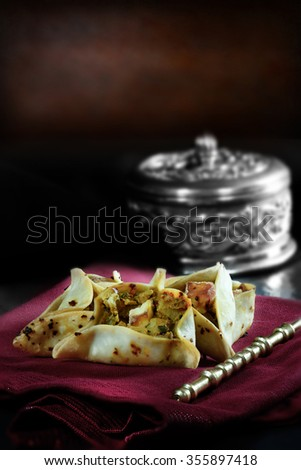 Paneer, aubergine and spiced chickpea open samosas against a rustic background with generous accommodation for copy space and selective focus. - stock photo
