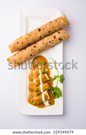 Paneer butter masala or Tikka Masala, Curry, Indian food, India,Folded homemade wheat chapati (Indian bread) served with delicious Indian paneer butter masala, isolated on white, white background  - stock photo