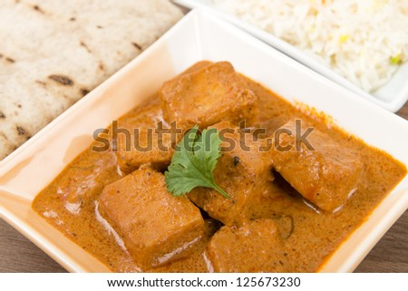 Paneer Makhani or Shahi Paneer (Paneer Butter Masala) - Indian curd cheese curry served garnished with coriander leaves and served with pilau rice and chapatis. - stock photo