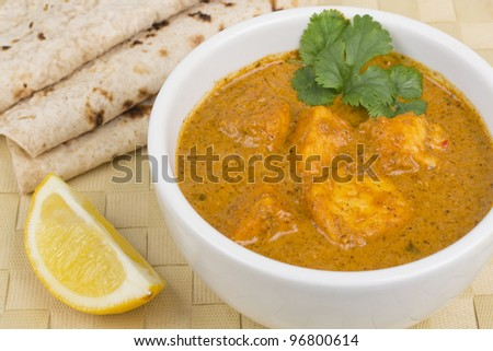 Paneer Makhani or Shahi Paneer (Paneer Butter Masala) - Indian curd cheese curry served with chapatis and a wedge of lemon. - stock photo