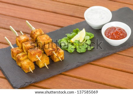 Paneer Tikka Kebab - Tandoori Indian cheese skewers served on a slate with lemon, chili sauce and cucumber and red onion yoghurt raita.
