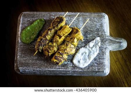 Paneer Tikka Kebab - Tandoori Indian cheese skewers served on a slate with lemon, chili sauce and cucumber and red onion yoghurt  - stock photo