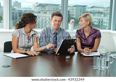Panel of business people sitting at table in meeting room conducting job interview. - stock photo